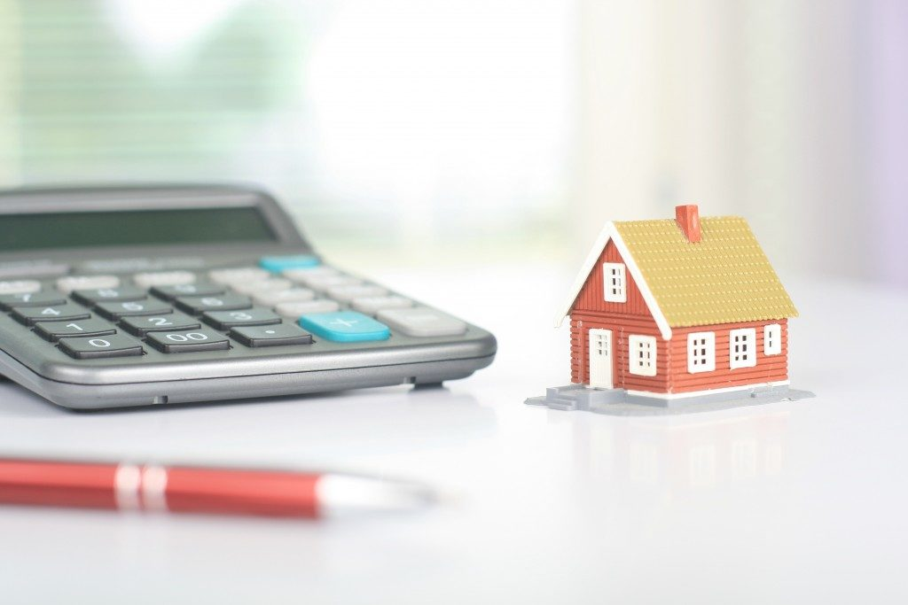 miniature house and calculator on a table