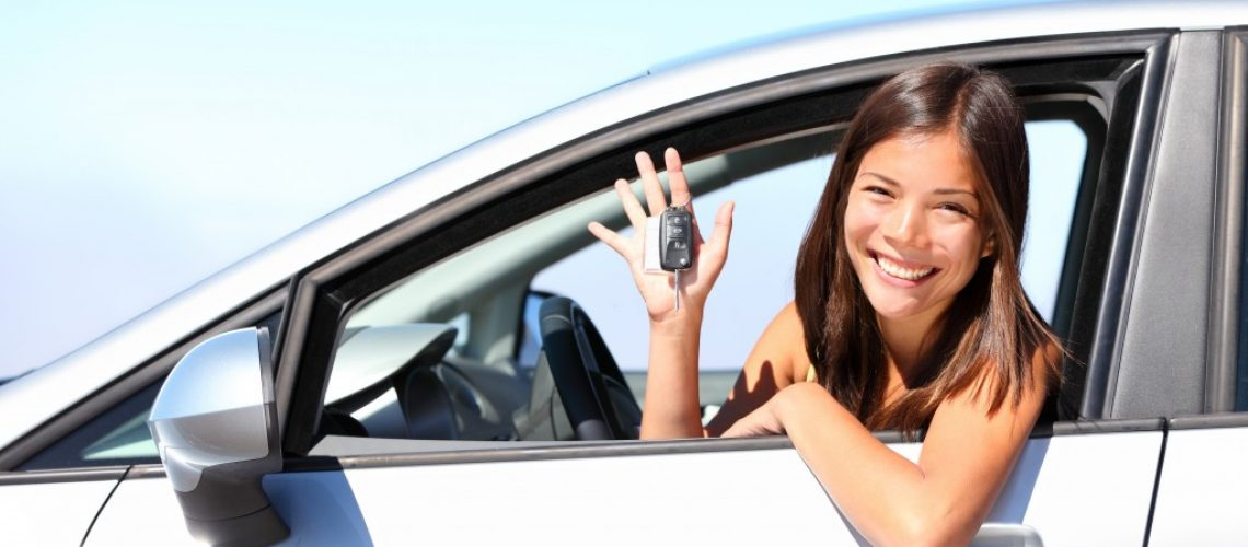 woman holding a car key inside the car